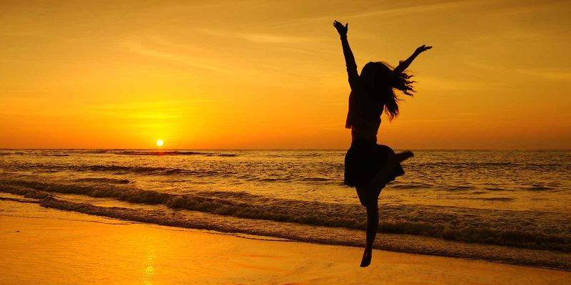 girl jumping on beach at sunset
