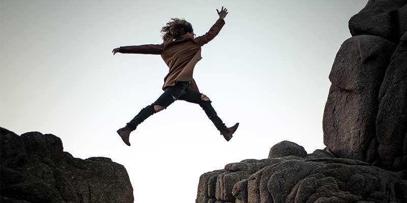 girl jumping gap between rocks