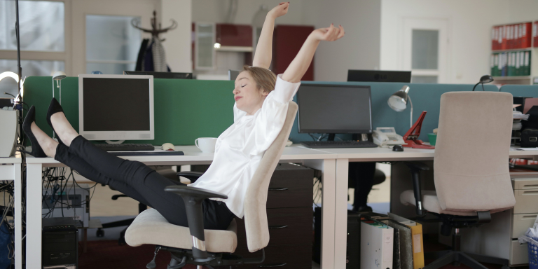 happy woman sitting at office desk