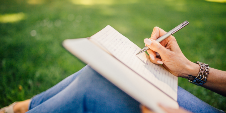 woman writing in journal on grass
